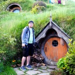 An average human male (Dan McBride) stands in front of a small Hobbit door.
