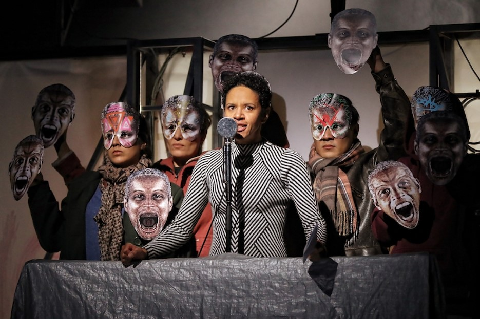 Actor Sara Zwangobani, surrounded by masked cast members, as Marc Antony in Julius Caesar.