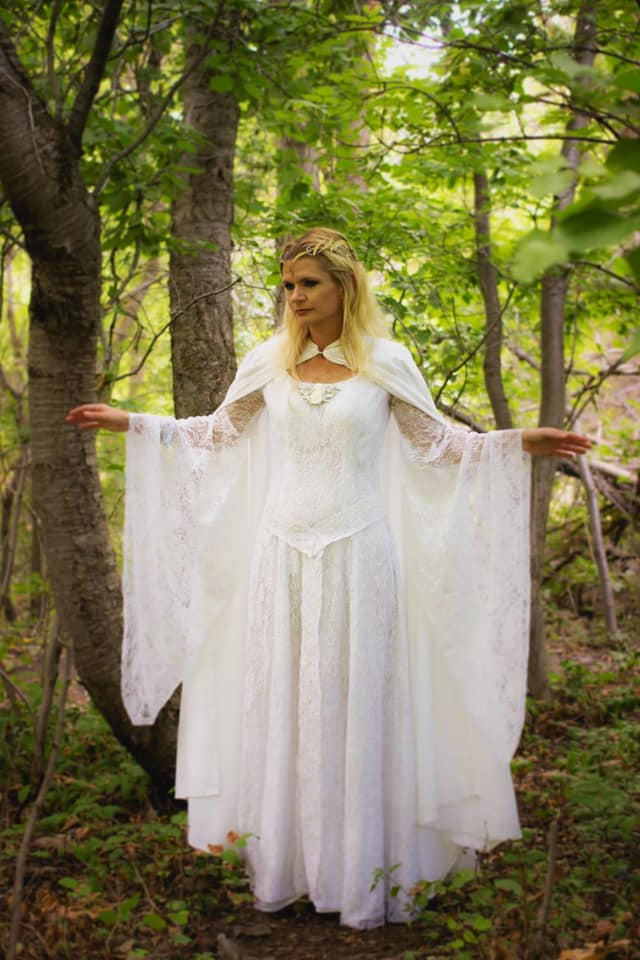 Fan Mindy in a gorgeous Galadriel costume she made. She is standing in a wooded clearing, looking like she's in Lothlorien!