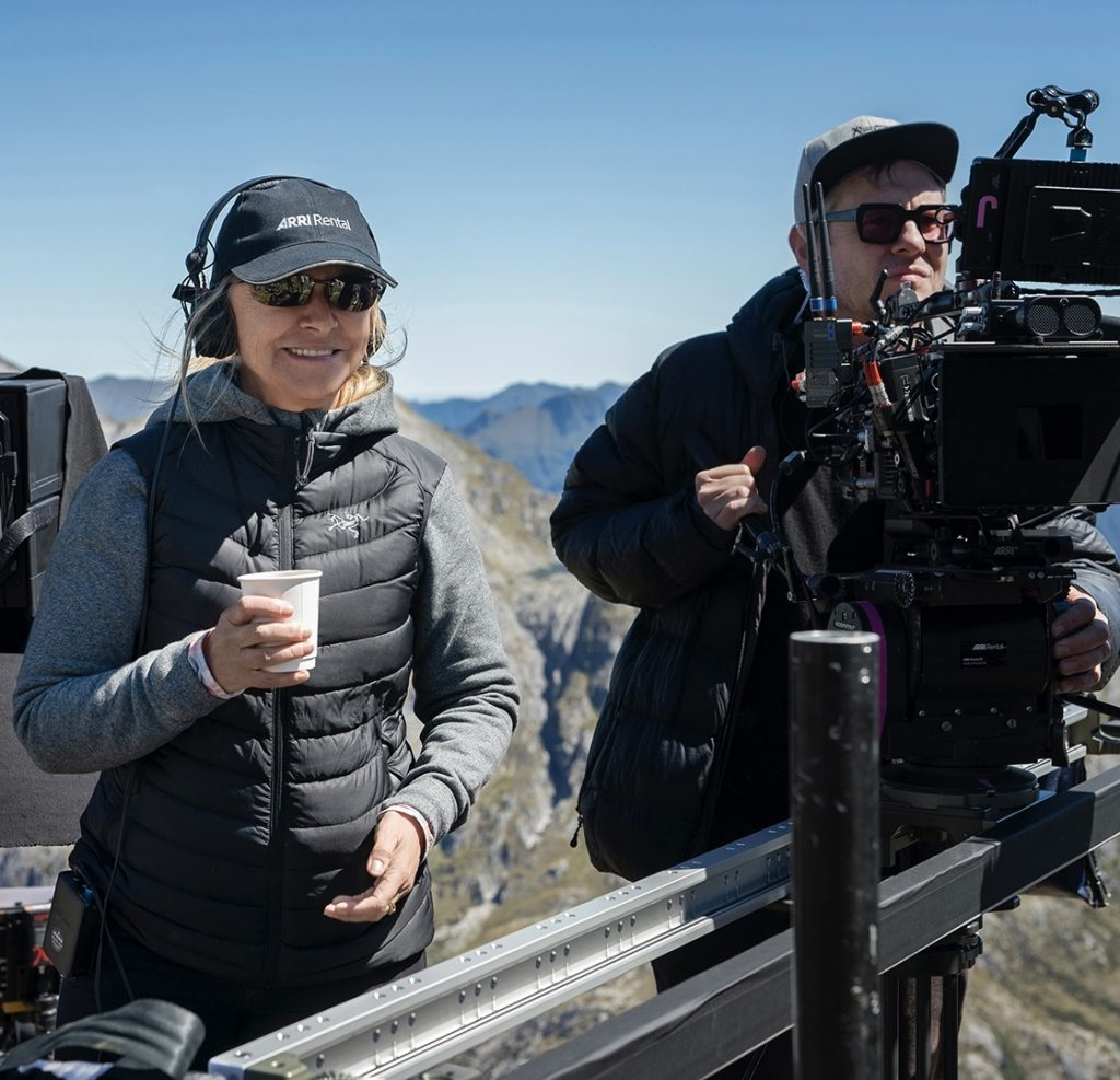 Director Charlotte Brändström, drink in hand, is seen with New Zealand scenery behind her and a camera operator on her left - on set for Amazon's Lord of the Rings tv show.