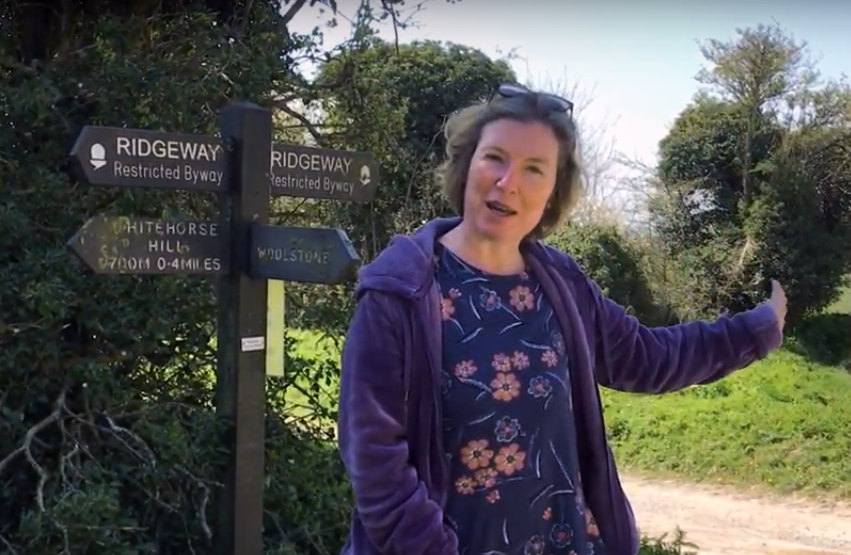 Julia Golding standing by a signpost on the Ridgeway in England.