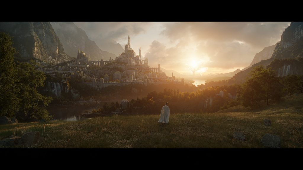 The first official image from Amazon's Lord of the Rings series. It shows a figure, perhaps an elf, cloaked in white, gazing towards a distant city. In the further distance we see the Two Trees, ablaze with light. Between the city and the trees there is an area of water.