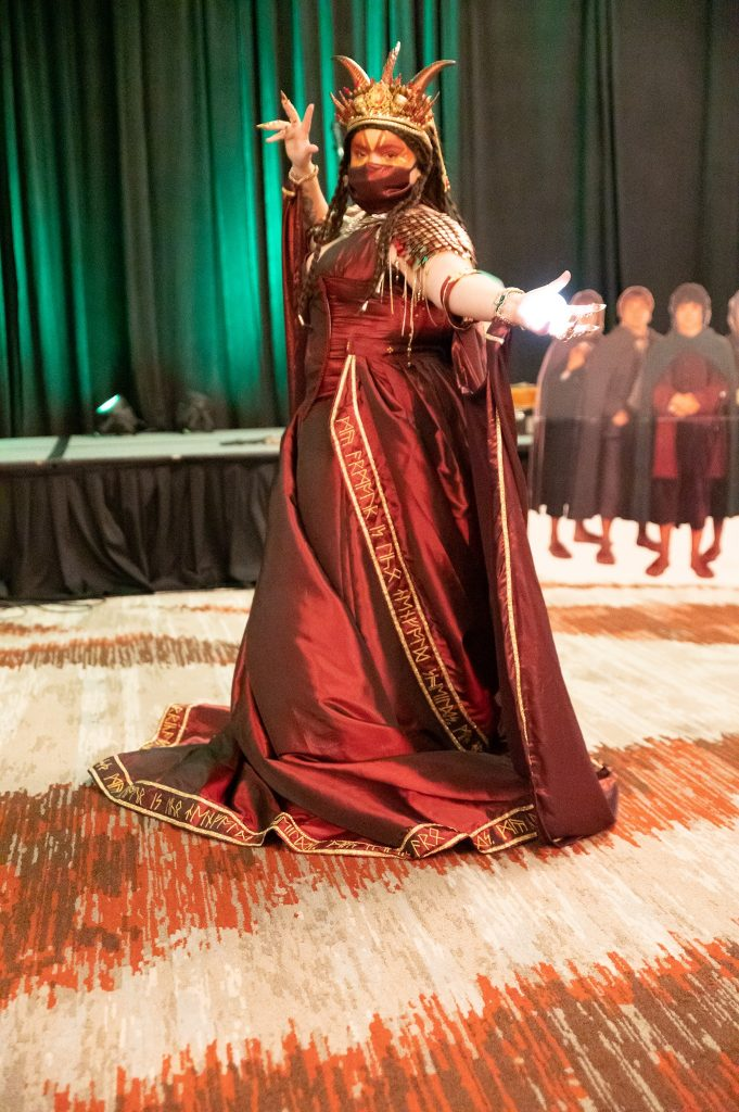 An amazing Smaug cosplay - a long, burgundy gown, with train edged with hand embroidered runes in gold. The dress includes scaled 'armour' epaulettes  in gold and burgundy, a flowing cloak, and  horned crown. The cosplayer has an illuminated Arkenstone in her hand, and long 'claw' fingernails.