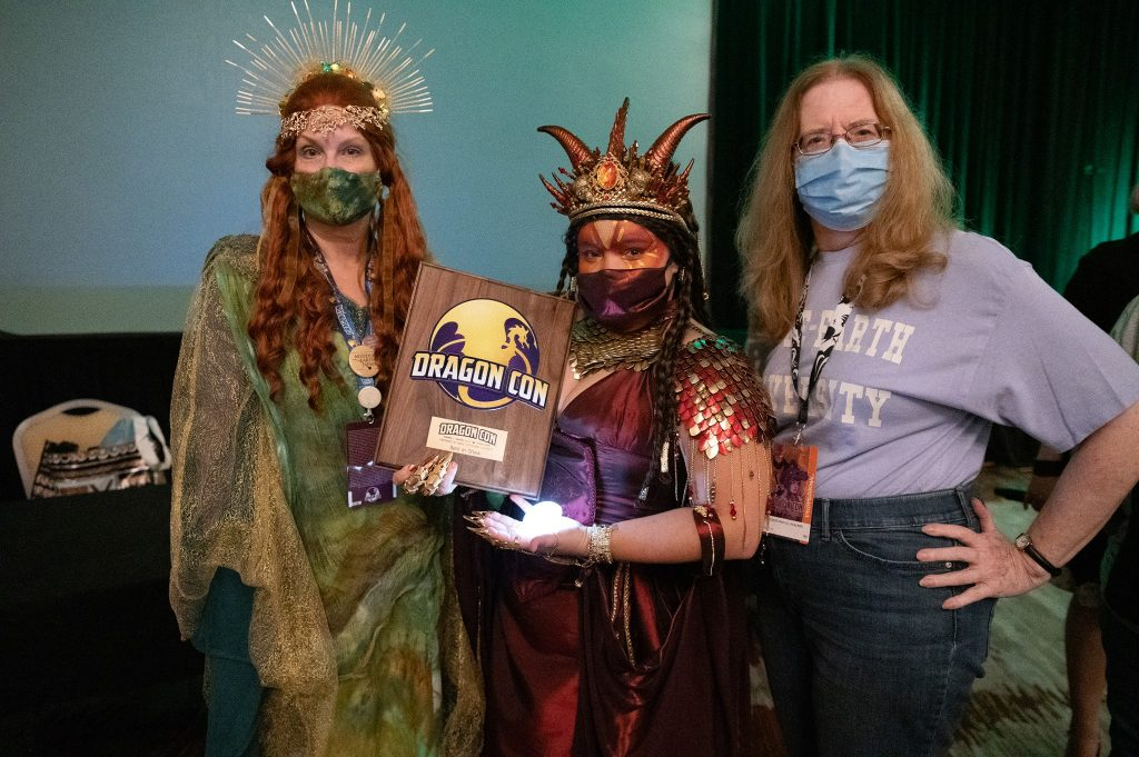 Best in Show winner in her Smaug gown is shown with her plaque award from DragonCon. On either side of her are costume contest judges Laura (L) and Constance (R). All are wearing masks over nose and mouth.